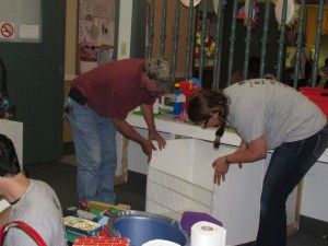 Avery Dennison's Mike Webster, left, and Susan Rhodes replace a bin in the playroom after  empting it of a jumble of toys and thoroughly washing it.