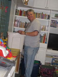 Kyle Rhodes, an Avery Dennison employee volunteering on Day of Caring at Forbes House, helps organize the shelter playroom.