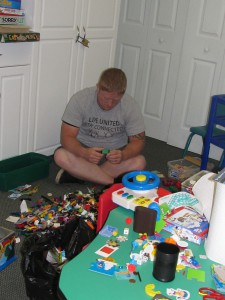 Ryan Lose takes a break from book duty and tries to organize Legos and other small toy pieces.