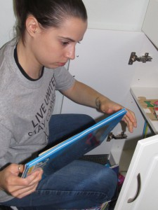 Day of Caring volunteer Frankie Masters stocks a kid's book in the Forbes House playroom.