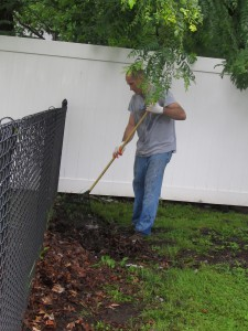 Dave Berrow, an Avery Denison Day of Caring volunteer, rakes leaves around the grounds at Forbes House.