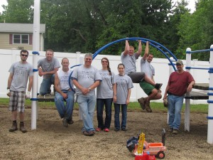 The United Way Day of Caring volunteers from Avery Dennison - James Baker, left to right,  Henry Milliman, Dave Berrow, Kyle Rhodes, Susan Rhodes, Frankie Masters, Ryan Lose, Josh  Bogner and Mike Webster - end their busy day at Forbes House by posing on the now weed- free playground many of them worked on once the rain stopped on June 25th. Some of the  team stayed inside shelter and finished their project in the playroom. Thanks volunteers for a job  well done!